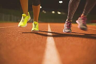 Athletes running on track on sports field