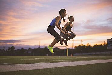 Athletes jumping on sports field