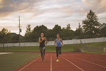 Athletes running on track in sports field
