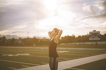 Caucasian athlete tying her hair up on sports field
