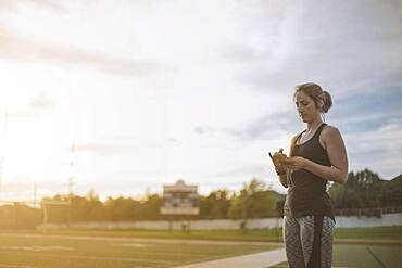 Caucasian athlete listening to mp3 player on sports field