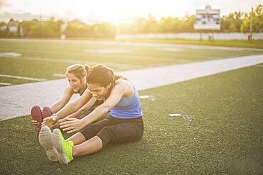 Athletes stretching on sports field