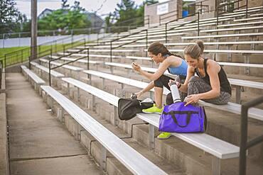 Women packing gym bags on bleachers