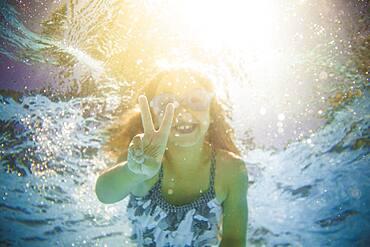 Caucasian girl swimming underwater gesturing peace sign