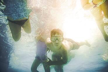 Children swimming underwater in swimming pool