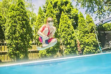 Caucasian boy jumping into swimming pool