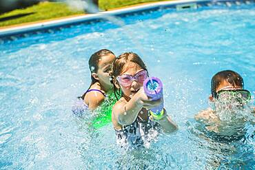 Children playing with squirt gun in swimming pool