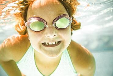 Caucasian girl swimming underwater in swimming pool