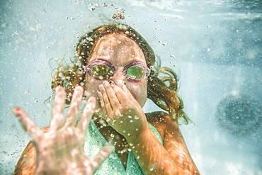 Caucasian girl holding nose underwater in swimming pool