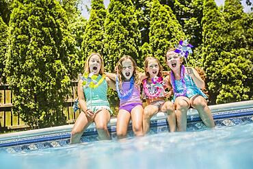 Caucasian girls cheering at swimming pool