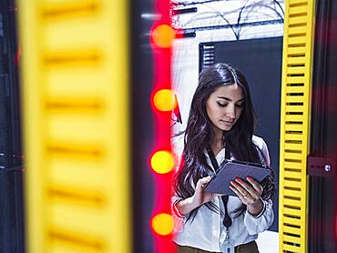 Mixed race technician using digital tablet in server room