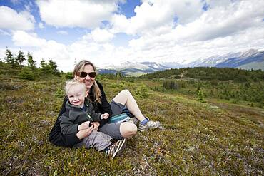Caucasian mother and son sitting on remote hilltop