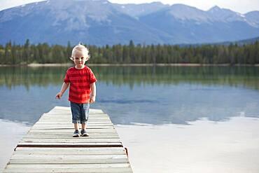 Caucasian boy walking on dock over remote lake