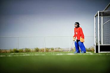 Mixed race field hockey goalie standing by goal