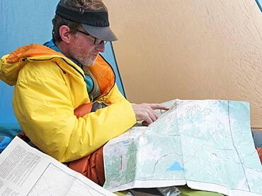 Caucasian man reading map in camping tent