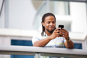 African American businessman using cell phone on balcony