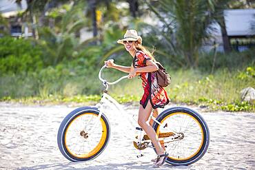 Hispanic woman riding bicycle on beach
