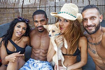 Friends smiling with dog in cabana
