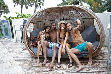 Friends taking selfie with cell phone in cabana