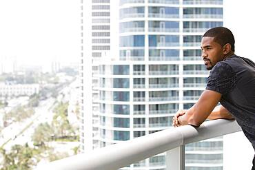 African American man standing on urban balcony