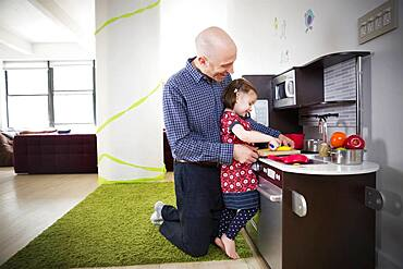 Father and daughter playing in toy kitchen