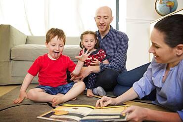 Family reading book on floor in living room