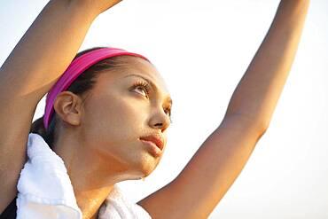 Hispanic woman stretching outdoors
