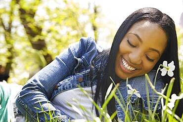 Black woman smiling in grass in park