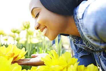 Black woman admiring flowers in park