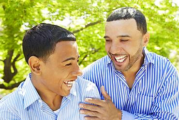 Hispanic father and son laughing in park