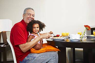 Grandfather and granddaughter eating breakfast at table