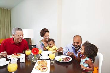 Multi-generation family eating breakfast at table