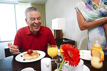 Father and daughter eating pancakes at table