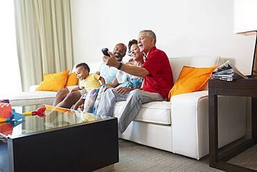 Multi-generation family taking selfie in living room