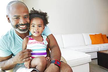 Black father and daughter sitting in living room