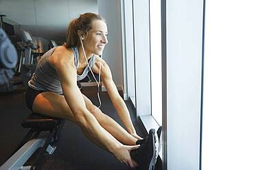 Smiling woman stretching in gym