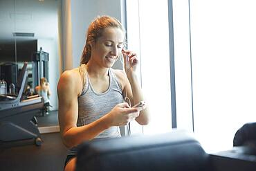 Woman listening to mp3 player in gym
