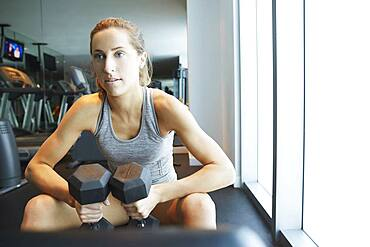Serious woman lifting weights in gym