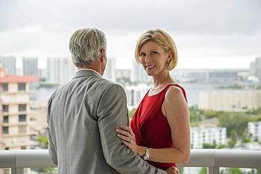 Caucasian couple hugging on balcony