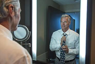 Caucasian businessman adjusting tie in mirror