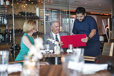 Waiter assisting couple with menu in restaurant