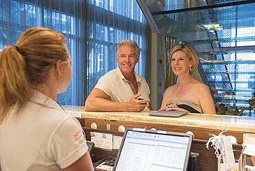 Caucasian couple checking into hotel