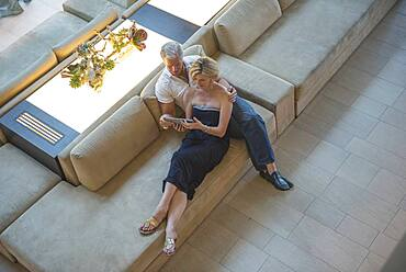 High angle view of Caucasian couple using digital tablet in hotel lobby