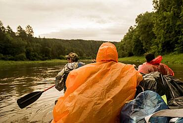 People wearing ponchos on boat in river