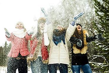 Caucasian girls tossing snow in air