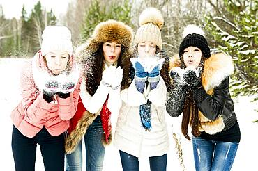 Caucasian girls blowing snow from hands