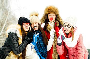 Caucasian girls playing with disguises in snow