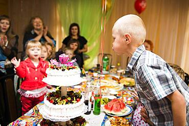 Caucasian boy blowing candles on birthday cake