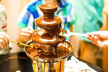 People eating from chocolate fountain
