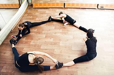 Caucasian dancers stretching in studio